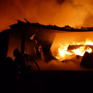 rozpadající se plechová hala zachvácená požárem